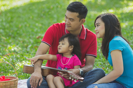 Cute little girl showing something with her finger to her mom and dad, over nature greenery