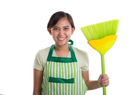 Smiling Asian woman with her green broomstick, isolated portrait over white background
