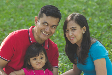 Happy Asian family closeup portrait over green grass natural outdoors background