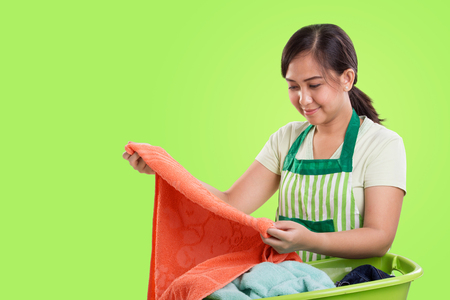 Young Asian mother handwash laundry, over bright green background with copyspace Stock Photo