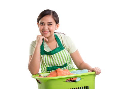 Smiling young woman resting on top of laundry basket and looking at camera, isolated on white background