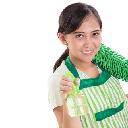 Closeup face of cleaning lady, holding a spray bottle and duster in green uniform, isolated over white
