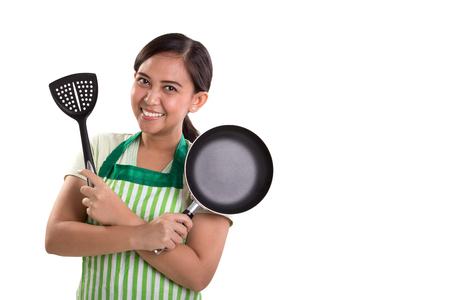 Hermosa mujer asiática sosteniendo utensilios de cocina con los brazos cruzados plantean, aislado en fondo blanco para el espacio de la copia