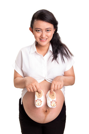 Attractive pregnant woman showing a pair of cute small shoes for her unborn baby, isolated over white