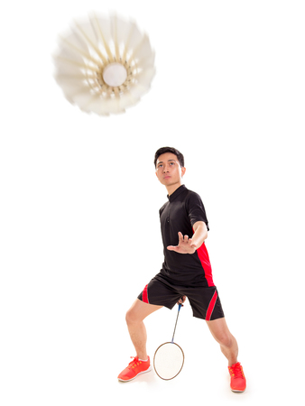 Shuttlecock coming and badminton player ready to do his trick. Isolated on white Stock Photo