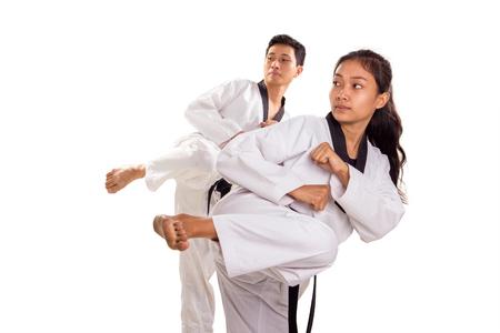 Male and female taekwondo athletes do kicking stances in sync, indoor portrait, isolated on white