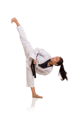 Taekwondo girl high kick, full length portrait isolated over white background