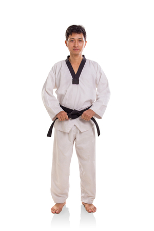 Full body portrait of martial art practitioner in his uniform standing over white background Stock Photo