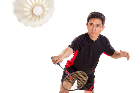 Badminton player ready to return the shuttlecock with backhand technique, isolated over white background Stock Photo