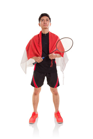 Indonesian badminton athlete standing with the flag wrapping on top of his shoulders, looking straight ahead. Full length. Isolated background Stock Photo