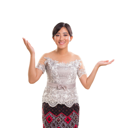 Portrait of an attractive young lady wearing a traditional costume of Java, Indonesia. She's smiling cheerfully and posing with both arms raised. Isolated over white background Reklamní fotografie