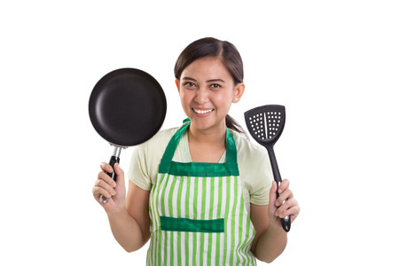 Friendly smiling young Asian mom showing her cooking utensils. Studio portrait on white