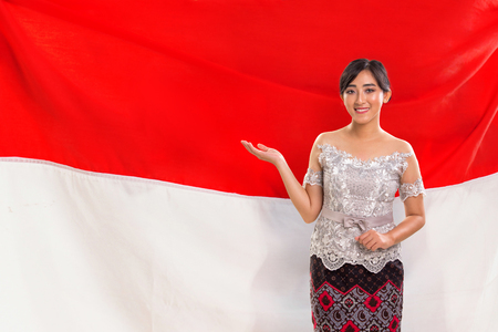 This is Indonesia: A beautiful young Asian female presenting with open arm, the country's red and white colored flag in the background