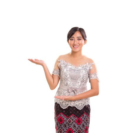 Giovane modella asiatica con posa di presentazione, indossando il moderno costume vintage Kebaya dell'Indonesia. Su sfondo bianco studio
