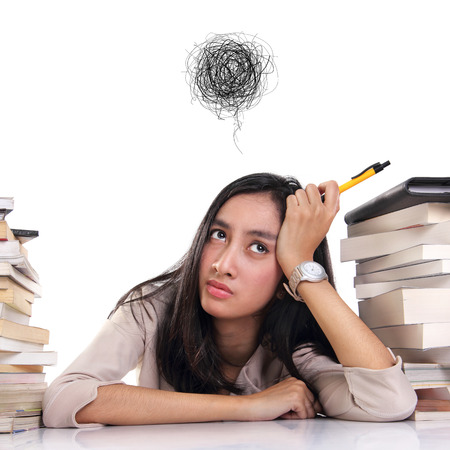 Frustrated young woman between two stacks of books on the desk. Tangled thread above her head. Conceptual portrait, isolated over white background