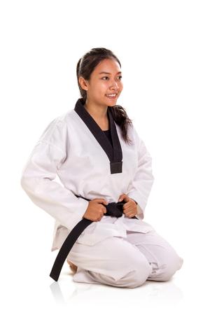 Beautiful smiling Asian female martial art fighter kneeling down pose, full length portrait on studio background 版權商用圖片