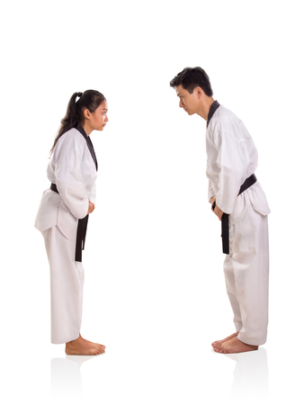 Full body side profile of female and male martial artists bowing down to each other to show respect, isolated on white background