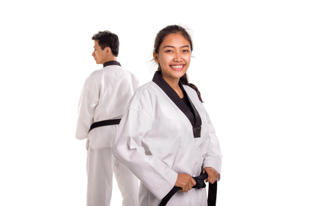 Close up shot of a cheerful female fighter wearing white traditional Gi, smiling at camera, her male partner standing on the background. Martial art concept portrait