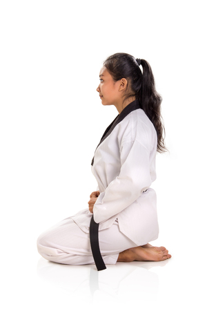 Side profile of a female martial art practitioner sits on her knees, isolated portrait, studio shot