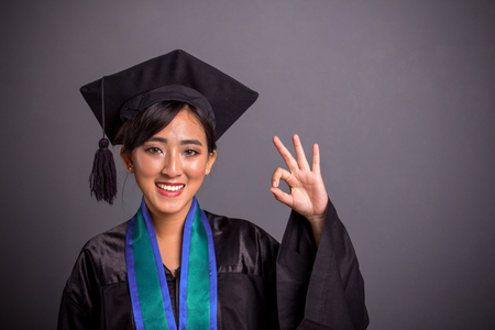 Happy smiling student girl dressed in graduation cap and gown, gesturing approval with her hand, over grey background Фото со стока