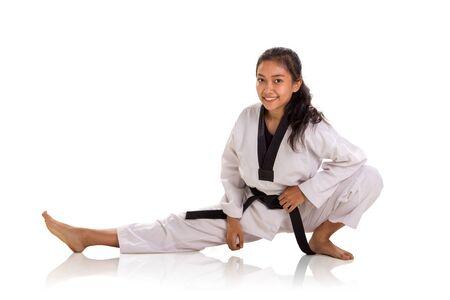 Luchadora alegre haciendo entrenamiento físico, estira la pierna derecha durante el calentamiento. Foto de estudio, retrato sobre fondo blanco.
