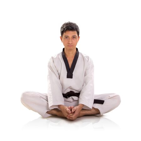Portrait of Asian man wearing traditional martial art costume sits in lotus position, looking at camera, white background