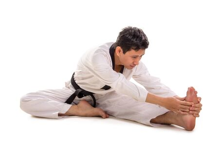 Martial artist stretches his body on the floor, bends his torso toward his leg, wraps a resistance band around his left foot. Full length shot