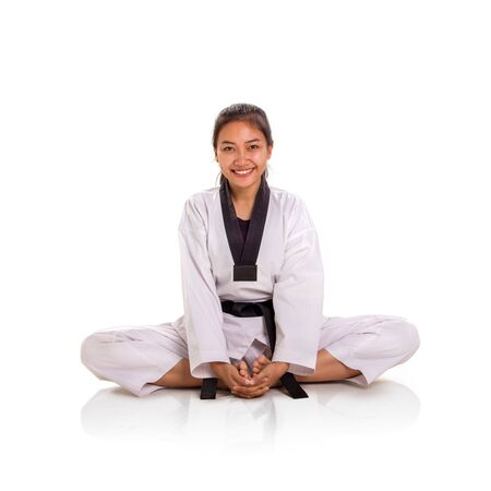 Portrait of attractive young Asian female fighter sitting in lotus position, smiling and looking at camera, over white background, studio shot Banco de Imagens