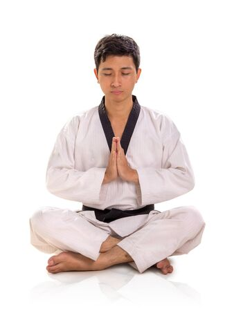 One male Asian martial artist meditating with legs crossed and hands pressed together on his chest, full length portrait isolated over white background Banco de Imagens