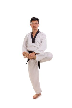 Full length shot of a martial artist doing warm-up stretching with his left leg lifted up, isolated over white background