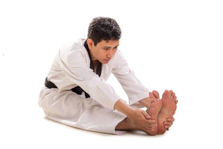 Pike position, a martial artist sits on the floor with legs out straight in front and hands grab onto his feet. Isolated full body portrait
