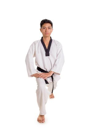 Portrait of a male karateka bending his knee, doing legs stretching before practice, front view full length portrait, isolated on white background Banco de Imagens