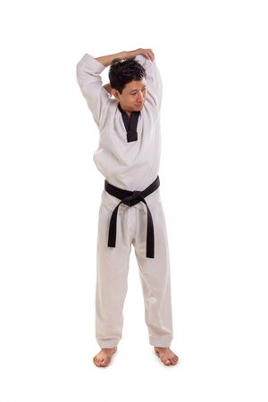 Full length shot of a male martial artist doing shoulder muscle stretching move, pulling arm behind his neck isolated over white background