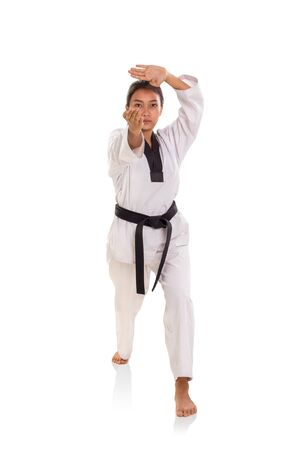 Female taekwondo athlete with thrusting hand strike stance, posing over white background Banco de Imagens