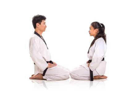 Portrait of two martial art practitioners sitting on their knees, facing each others. Full length, side view, studio shot