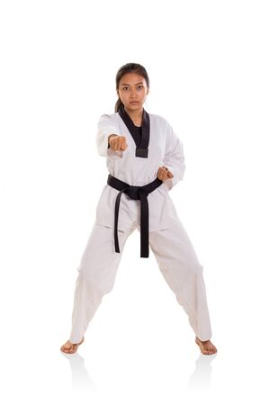 Portrait of a black belt female fighter practicing straight punch, standing over white background, front view Banco de Imagens