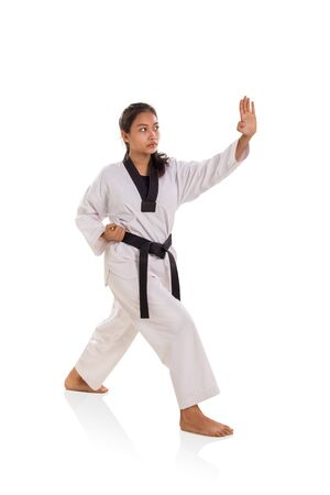 Full length shot of female martial artist striking with left hand palm, isolated on white background