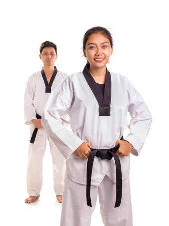 Attractive female tae-kwon-do athlete posing with her male training partner standing behind her, isolated over white background Banco de Imagens