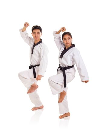 Two professional athlete showing a tae-kwon-do move, standing over white background, full length portrait Banco de Imagens