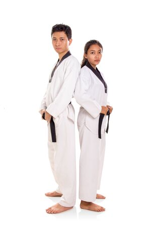 One couple of taekwondo masters leaning back against each other, standing over white background, full length portrait