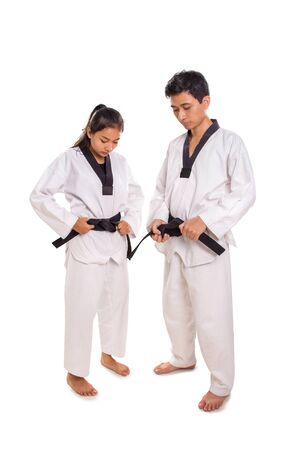 Full length portrait of female and male martial artists putting on their uniforms, isolated on white background Banco de Imagens