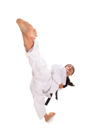 Young female taekwondo master showing her high kick technique, full length shot isolated over white background
