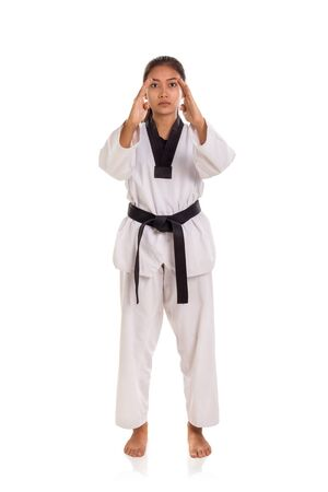Tae-kwon-do girl in her ready stance with two hands open, full length portrait, front view, white background