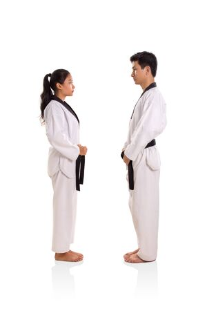 Female and male martial art practitioners standing, facing against each others, full body side profile isolated on white background