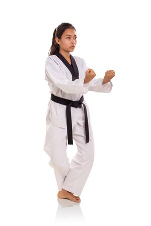 Female traditional martial artist standing with double knuckle and crossed legs pose, isolated on white background