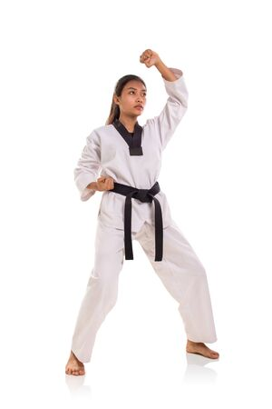 Female martial artist doing upper strike block move with her forearm, full body shot on white background Banco de Imagens