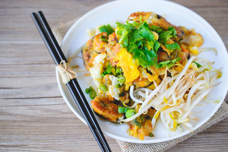 fried mussel pancake with old wooden background, Thai Cuisine, Thai Food