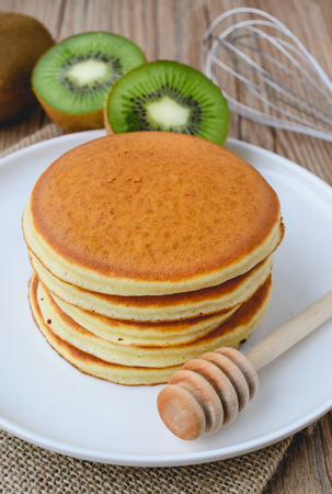 sackcloth: stack of pancake on white plate and sackcloth with kiwi slices on wood background