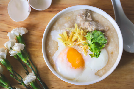 rice porridge with ground pock vintage tone with white flowers on wood background, Thai Food, Thai Cuisine, Beast Breakfast