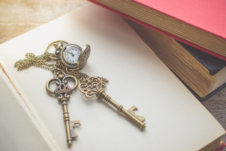 Old vintage key on  stack of old book with copy space in morning light for unlock or eductaion concept Banco de Imagens